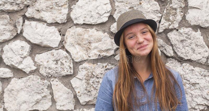Leuk tienermeisje op de achtergrond van de steenmuur gelukkig royalty-vrije stock foto's