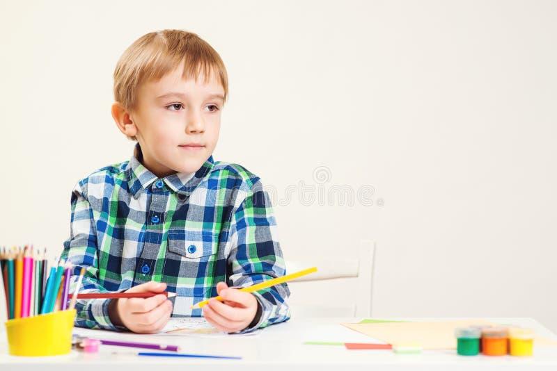 Leuk trekt weinig jongen met potloden in opvangcentrum Creatieve jong geitjeklasse Kinderen, hobby, kinderjaren en gelukkig mense stock afbeelding