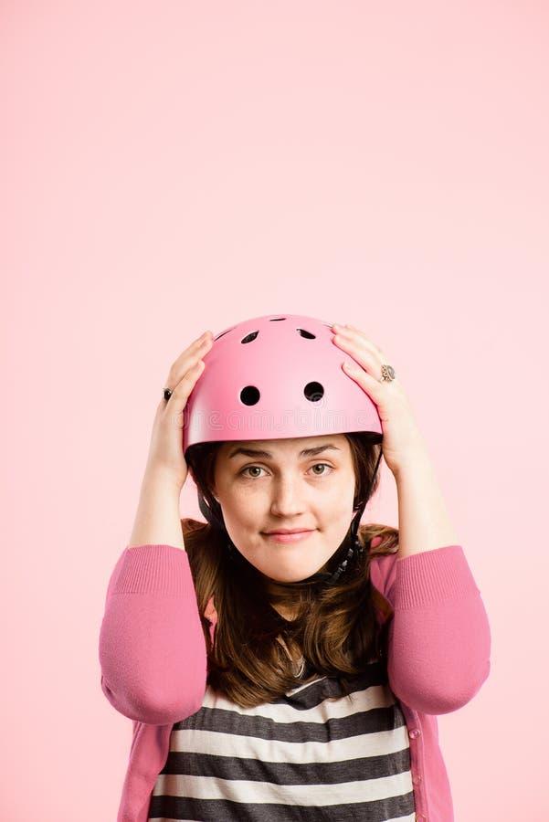 Grappige vrouw die het Cirkelen echte het portret roze achtergrond dragen van de Helm stock foto's
