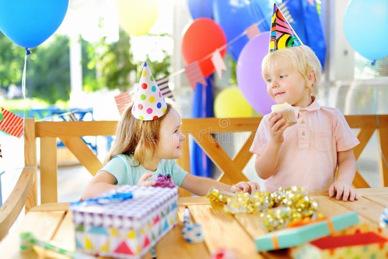 Leuk vieren weinig jongen en meisje die pret hebben en verjaardagspartij met kleurrijke decoratie en cake royalty-vrije stock fotografie