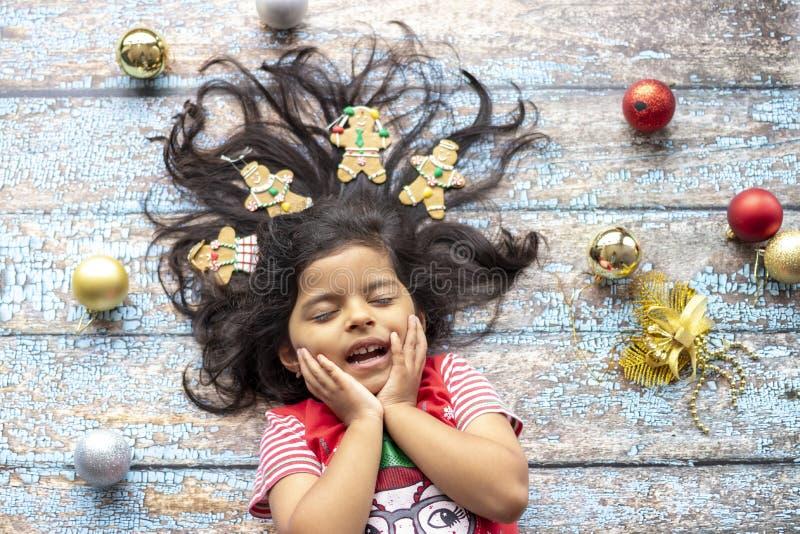 Leuk vrolijk glimlachend meisje met verfraaid Kerstmishaar met peperkoekmensen royalty-vrije stock fotografie