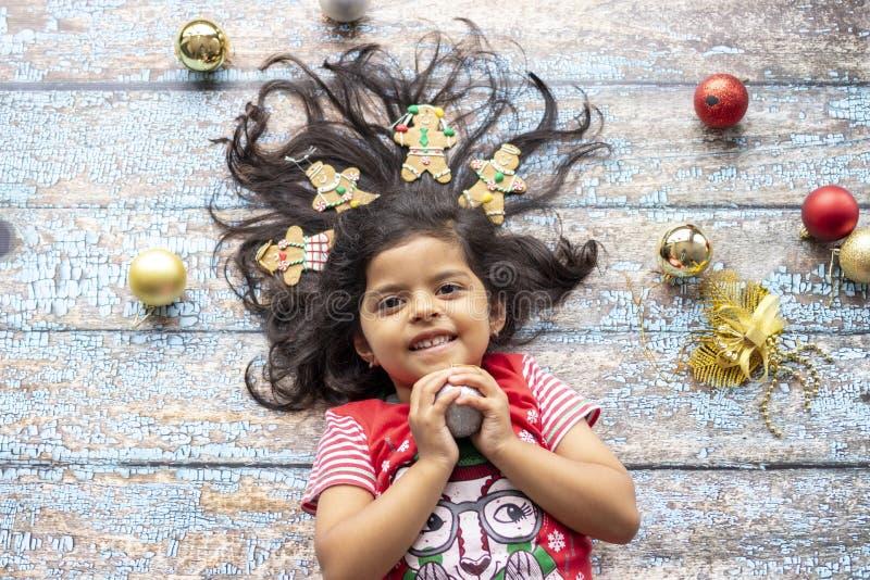 Leuk vrolijk glimlachend meisje met verfraaid Kerstmishaar met peperkoekmensen stock foto's