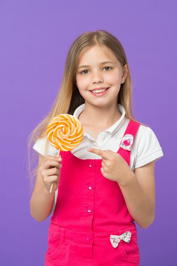 Leuk vrolijk meisje die reuzesuikergoed houden Jong geitje met lang blond die haar op violette achtergrond wordt geïsoleerd Kind  stock afbeeldingen