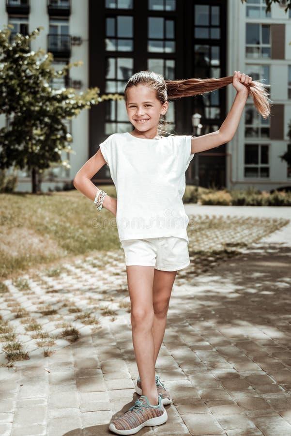 Leuk vrolijk positief meisje die haar paardestaart houden stock foto