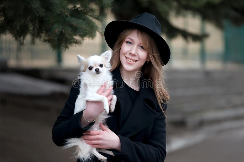 Leuk vrolijk slank Kaukasisch meisjesblonde met lang haar in een zwarte laag en een zwarte hoed binnen in de de herfstdag met haa royalty-vrije stock fotografie