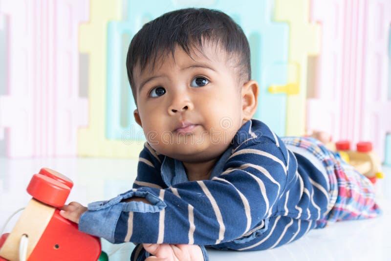 Leuk weinig Aziatisch babyjongen het liggen houten spelstuk speelgoed royalty-vrije stock foto's