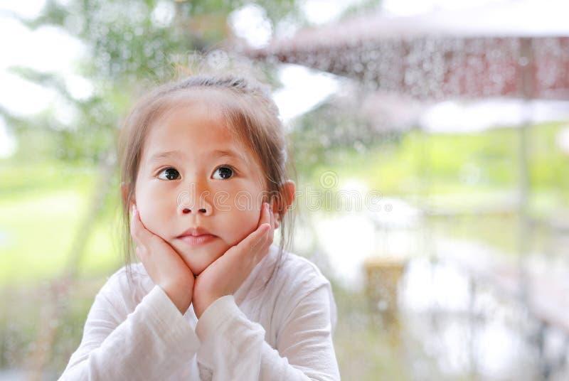 Leuk weinig Aziatisch gebaar van het kindmeisje met vreedzaam gezicht tegen glasvenster met waterdaling bij regenachtige dag royalty-vrije stock foto