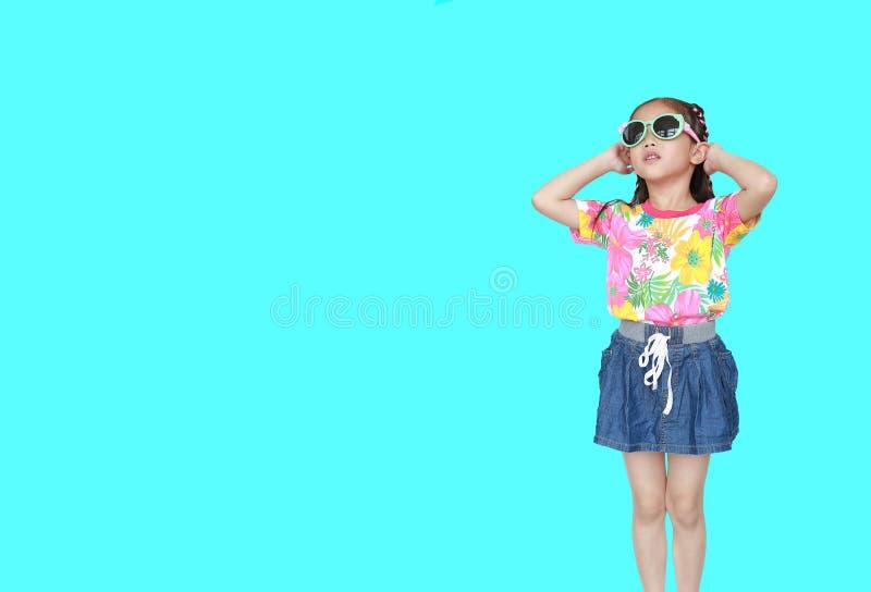 Leuk weinig Aziatisch jong geitjemeisje die een kleding en de zonnebril dragen die van de bloemenzomer op cyaanachtergrond wordt  royalty-vrije stock foto's