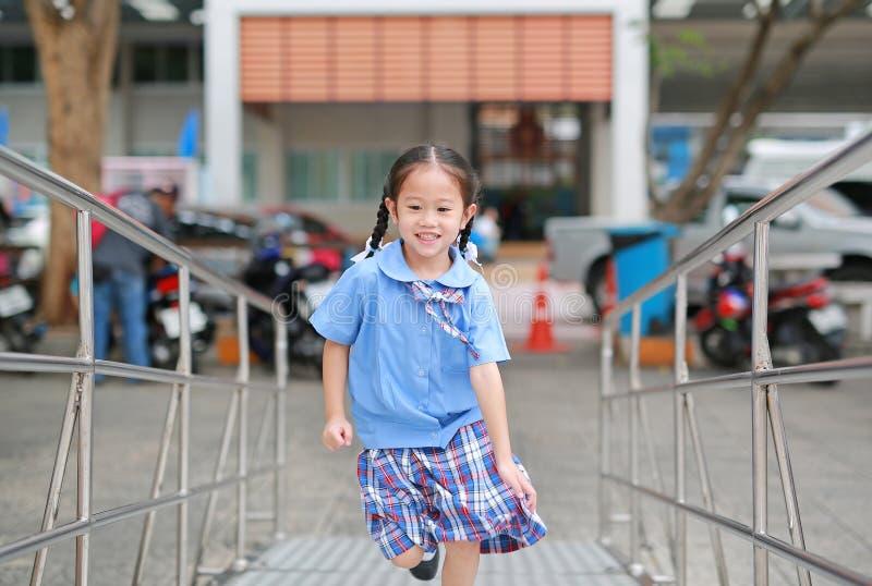 Leuk weinig Aziatisch kindmeisje in school eenvormige het lanceren metaaltrede stock foto's