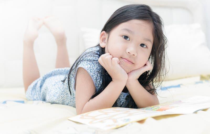 Leuk weinig Aziatisch meisje die in nachtjapon een boek lezen royalty-vrije stock afbeelding