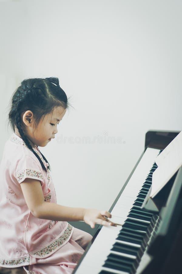 Leuk weinig Aziatisch meisje in het traditionele Chinese kleding pian spelen royalty-vrije stock afbeelding