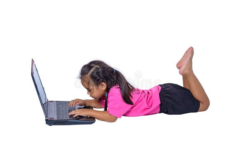 Leuk weinig Aziatisch meisjeskind die op de vloer liggen die die of laptop bestuderen met behulp van op witte achtergrond met het royalty-vrije stock foto