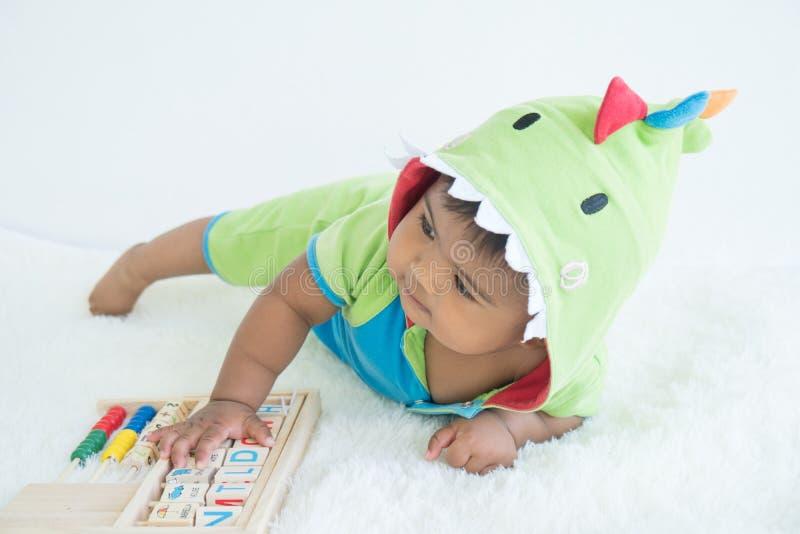 Leuk weinig Aziatische baby in groen kostuum stock afbeeldingen