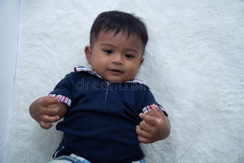 Leuk weinig Aziatische babyjongen die op zachte deken liggen stock afbeeldingen