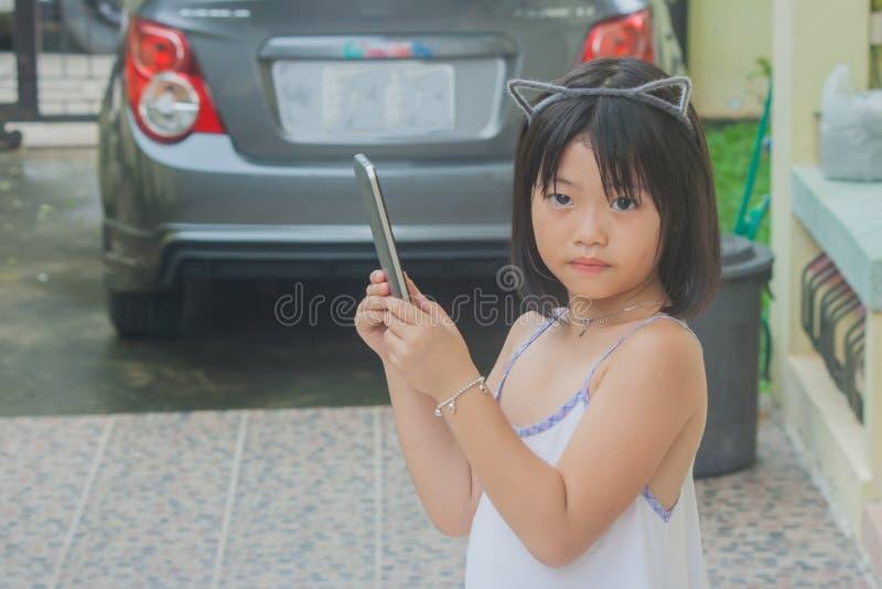 Leuk weinig Aziatische Chinese meisje het spelen smartphone stock afbeeldingen
