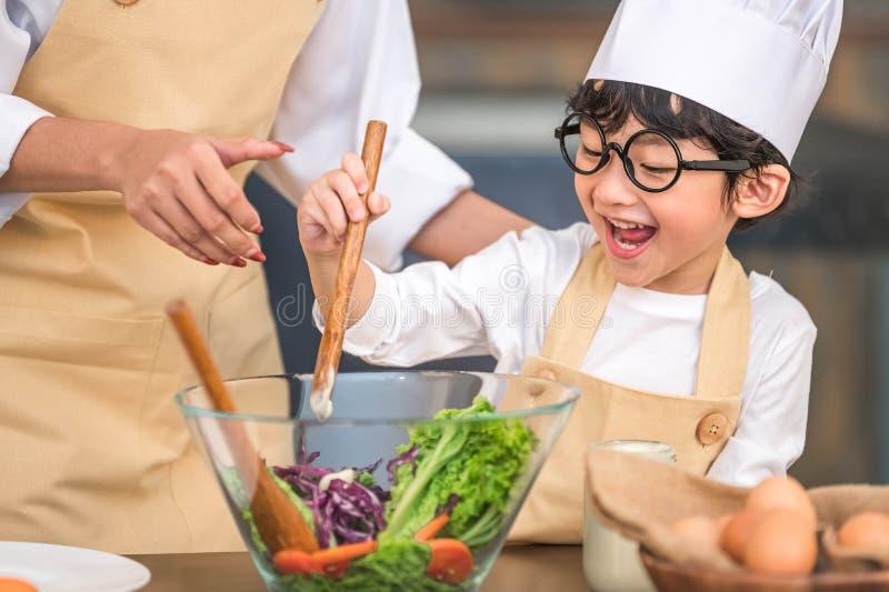 Leuk weinig Aziatische gelukkige jongen geinteresseerd in het koken met moeder grappig in huiskeuken Mensenlevensstijlen en Famil royalty-vrije stock foto