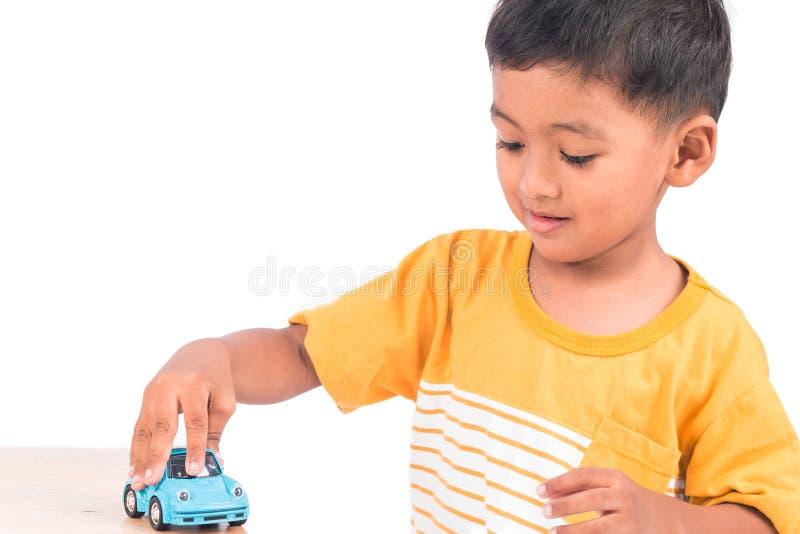 Leuk weinig Aziatische het jonge geitjekleuter van het jongenskind het spelen stuk speelgoed auto royalty-vrije stock foto