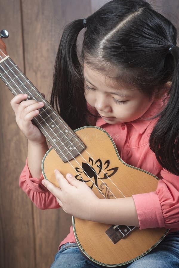 Leuk Weinig Aziatische Meisje het spelen ukelele royalty-vrije stock afbeeldingen