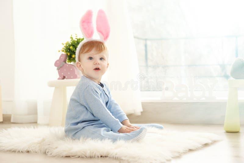 Leuk weinig baby die konijntjesoren dragen die op vloer zitten royalty-vrije stock afbeelding