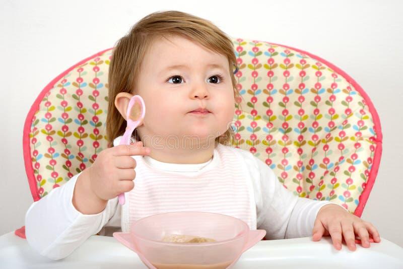 Leuk weinig baby die met lepel eten stock afbeelding