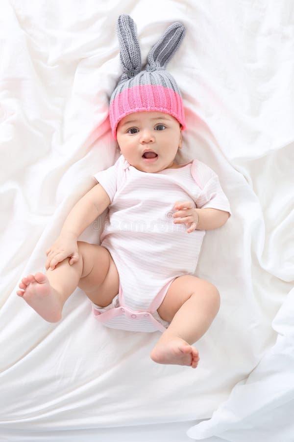 Leuk weinig baby die op bed thuis liggen stock fotografie