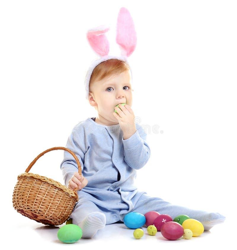 Leuk weinig baby in konijntjesoren en mand met paaseieren royalty-vrije stock afbeeldingen