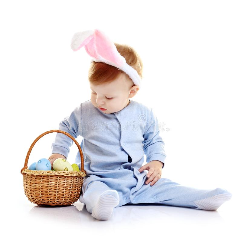 Leuk weinig baby in konijntjesoren en mand met paaseieren stock foto's