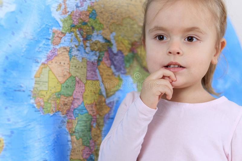 Leuk weinig baby met dromerig gezicht op de achtergrond van de wereldkaart stock foto