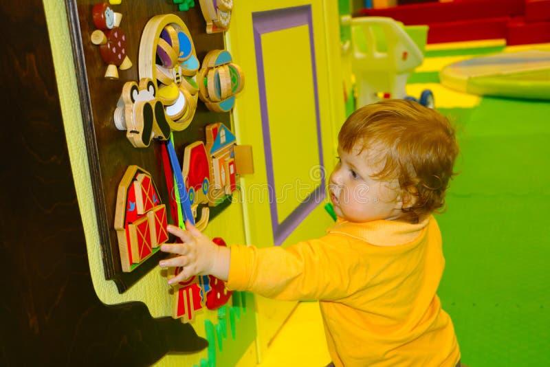 Leuk weinig baby met gemberhaar het spelen met busyboard in royalty-vrije stock afbeelding