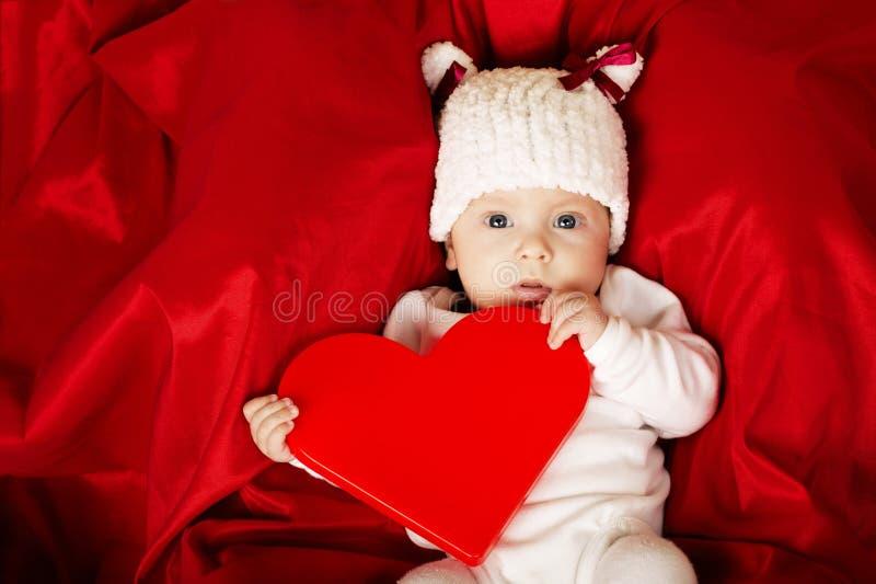 Leuk weinig baby met hart stock afbeelding
