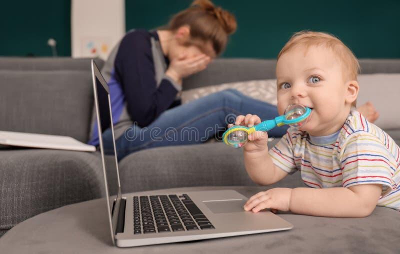 Leuk weinig baby met laptop met vermoeide moeder thuis stock fotografie