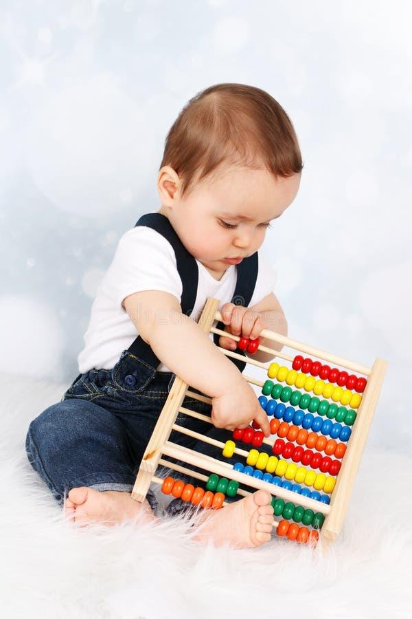 Leuk weinig babyjongen die met telraam spelen stock fotografie