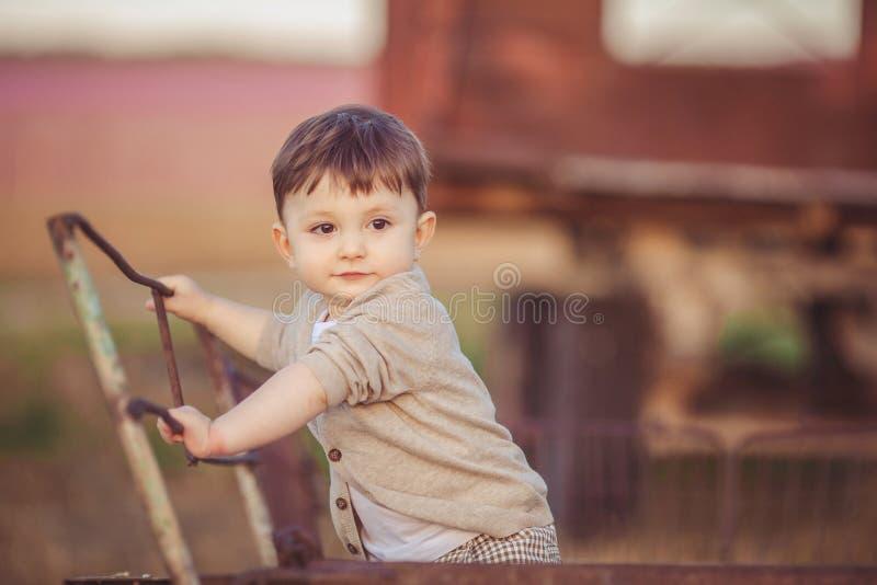 Leuk weinig babyjongen die zich dichtbij metaalomheining bevinden in de herfstwerf royalty-vrije stock fotografie