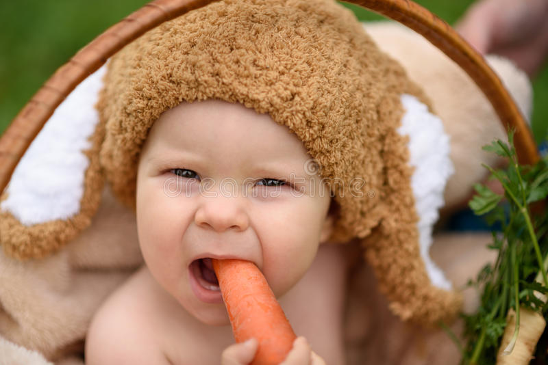 Leuk weinig babyjongen in kostuum van konijnzitting op het gras in mand die kool en wortel eten stock afbeeldingen