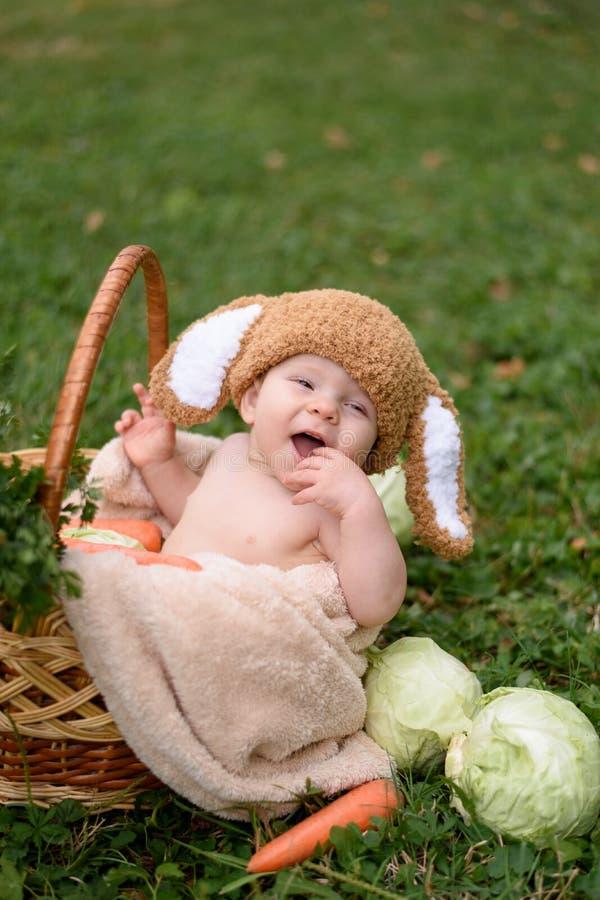 Leuk weinig babyjongen in kostuum van konijnzitting op het gras in mand met kool en wortel stock fotografie