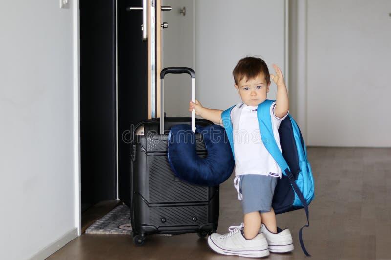 Leuk weinig babyjongen in vaderstennisschoenen en met de grote koffer van de rugzakholding en het golven van vaarwel klaar het bl royalty-vrije stock fotografie