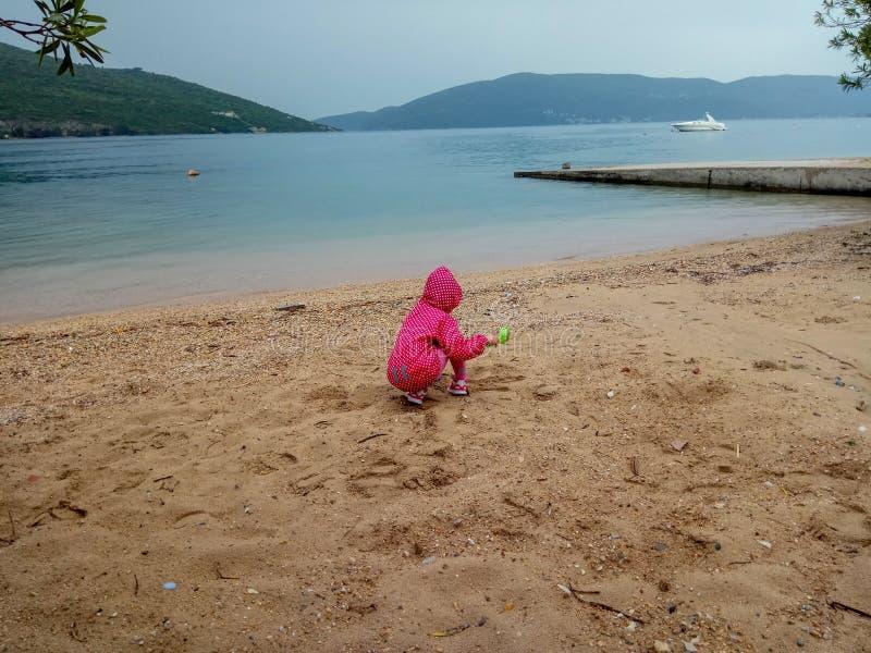 Leuk weinig babymeisje die met het zand bij het strand in een stormachtig weer spelen stock foto