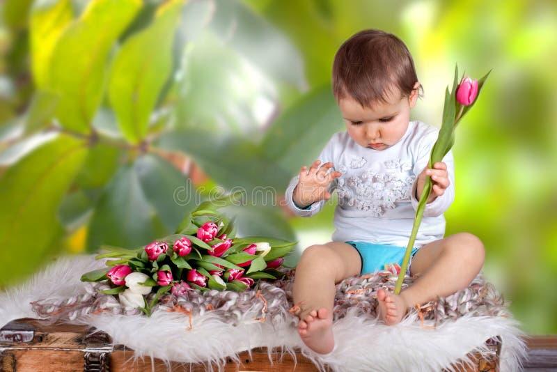 Leuk weinig babymeisje met tulpen royalty-vrije stock fotografie