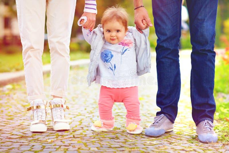 Leuk weinig babymeisje op gang met ouders, eerste stappen stock fotografie