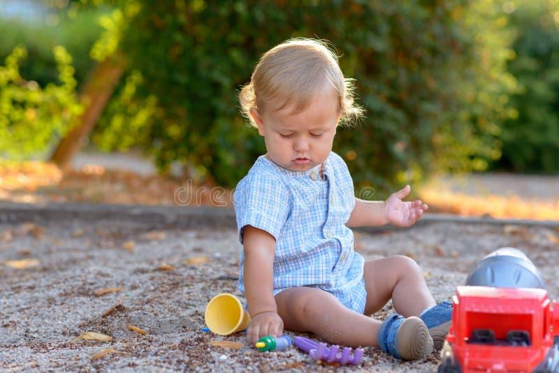 Leuk weinig blonde babyjongen die in openlucht spelen royalty-vrije stock foto's