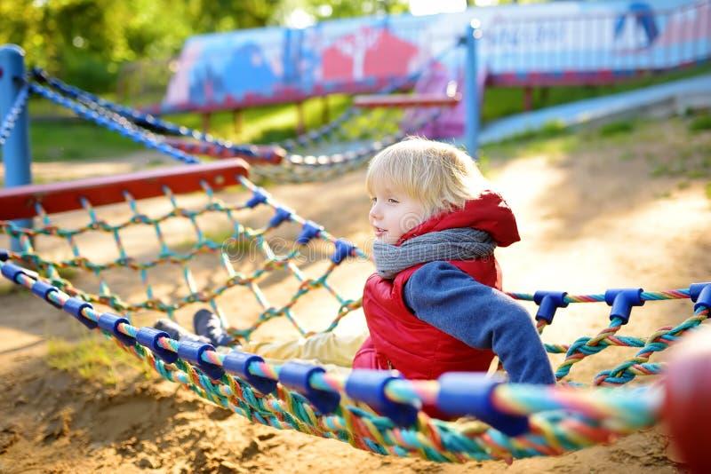Leuk weinig blonde Kaukasische jongen die pret op openluchtspeelplaats hebben Actieve sportvrije tijd voor jonge geitjes Kind op  royalty-vrije stock foto