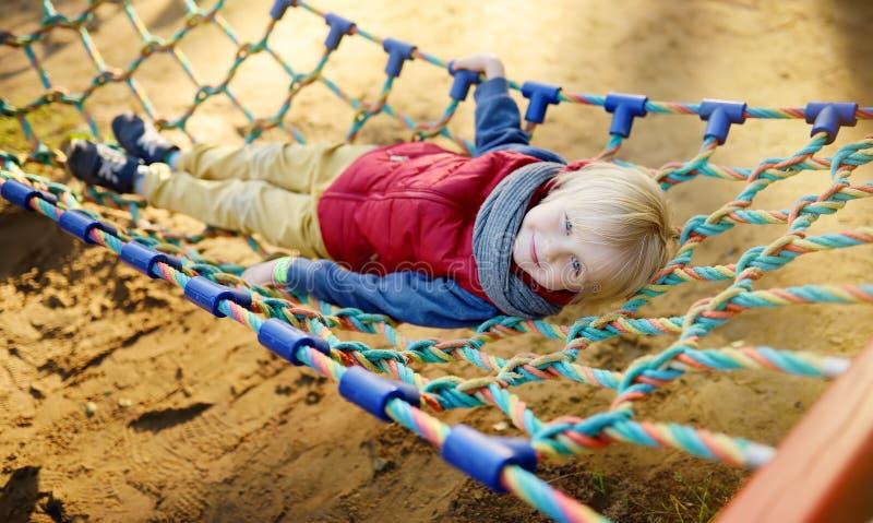 Leuk weinig blonde Kaukasische jongen die pret op openluchtspeelplaats hebben Actieve sportvrije tijd voor jonge geitjes Kind op  royalty-vrije stock foto's