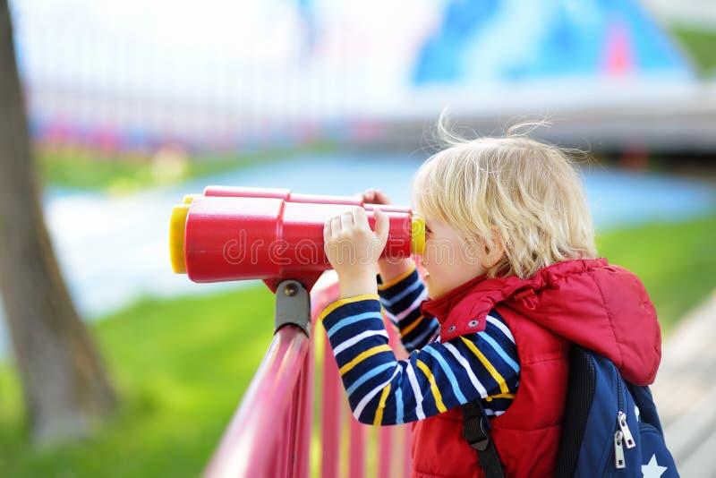 Leuk weinig blonde Kaukasische jongen, jong geitje of kind die door verrekijkers op speelplaats in openlucht kijken royalty-vrije stock fotografie