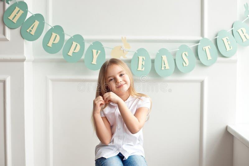 Leuk weinig blonde meisjeszitting in een heldere ruimte dichtbij het venster op de achtergrond van wimpels met de inschrijving stock foto