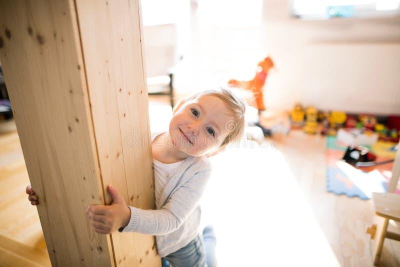 Leuk weinig blondemeisje thuis bij de houten straal royalty-vrije stock afbeeldingen