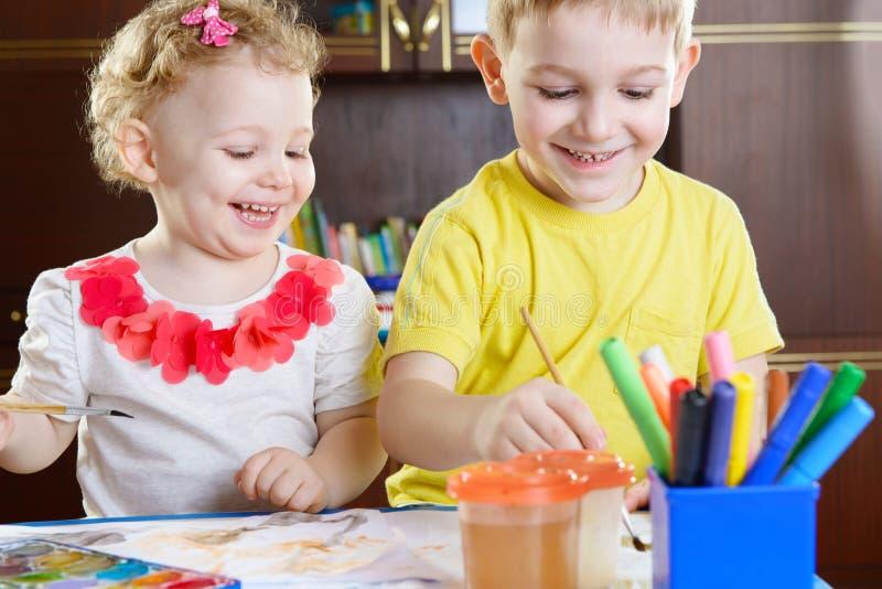 Glimlachend weinig broer en zuster die thuis schilderen stock afbeelding