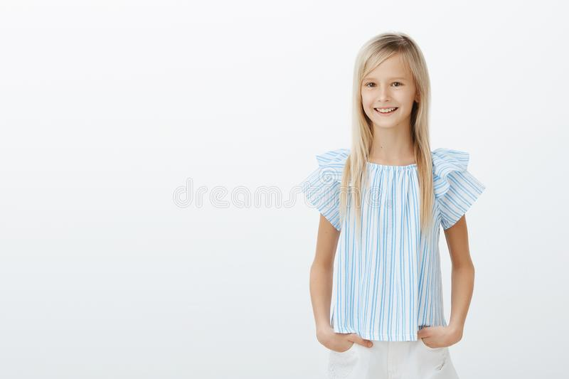 Leuk weinig dame die met mamma winkelen Studioportret die van tevreden gelukkig vrouwelijk kind in blauwe blouse, handen op heupe stock fotografie
