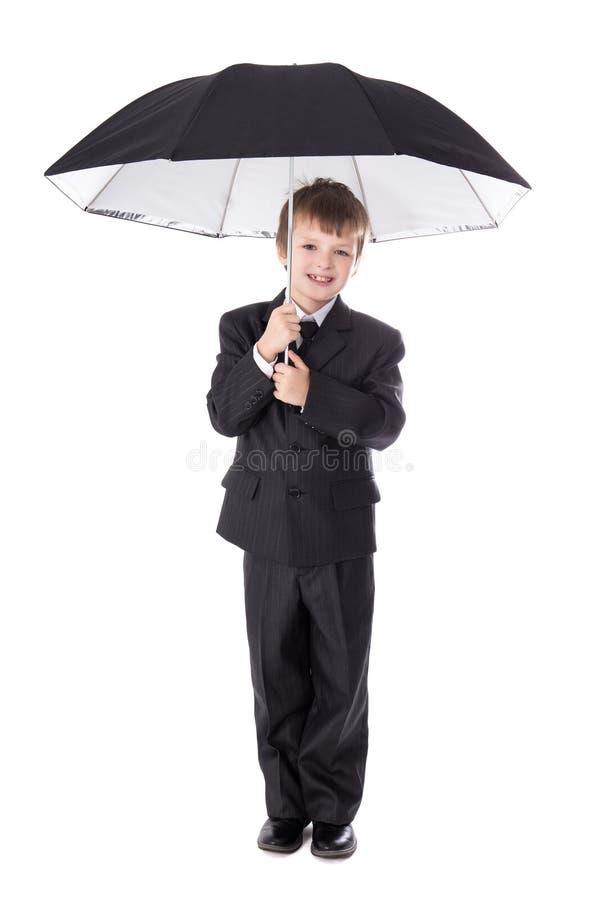 Leuk weinig die jongen in pak met paraplu op wit wordt geïsoleerd royalty-vrije stock afbeeldingen