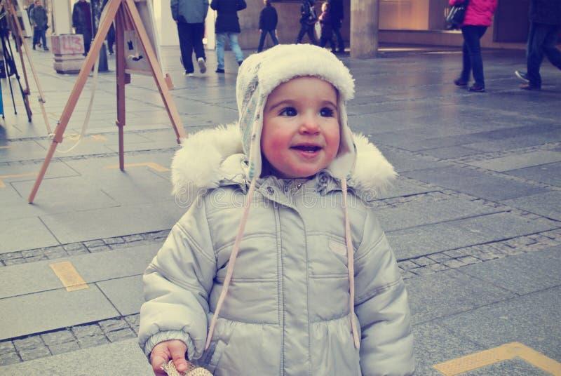 Leuk weinig glimlachend meisje op de straat in de winter; retro Instagram-stijl stock fotografie