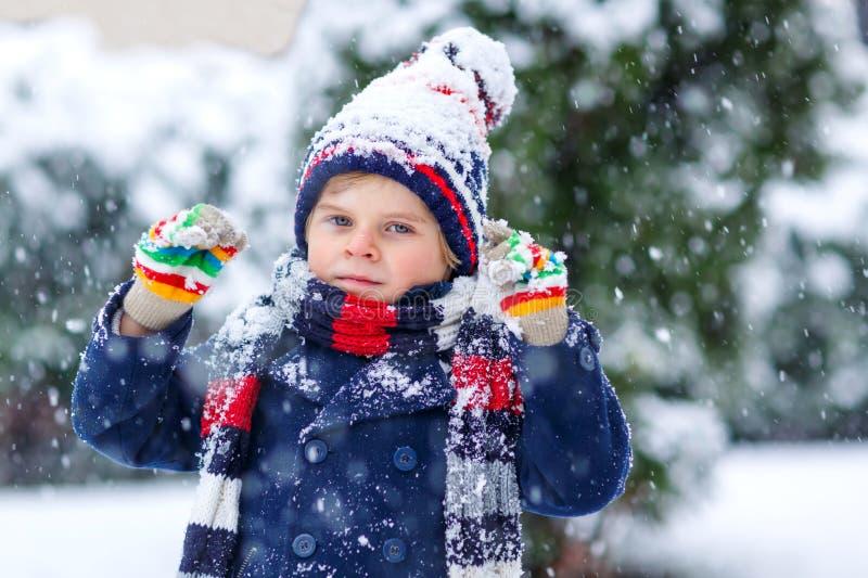 Leuk weinig grappig kind in de kleurrijke kleren die van de de wintermanier pret hebben en met sneeuw, in openlucht tijdens sneeu royalty-vrije stock fotografie